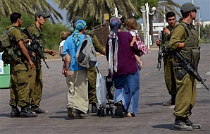Settlers walk past idf